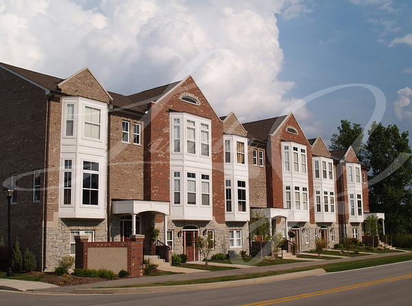 A row of brick condos or townhouses with bay windows beside a street.