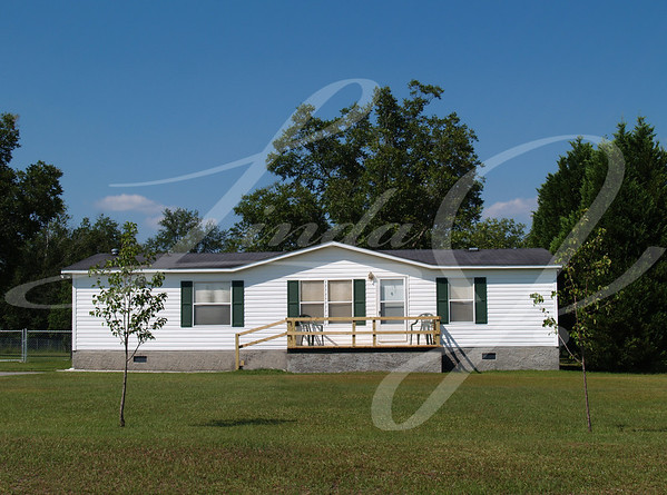 White single-wide mobile residential low income home with vinyl siding on the facade.