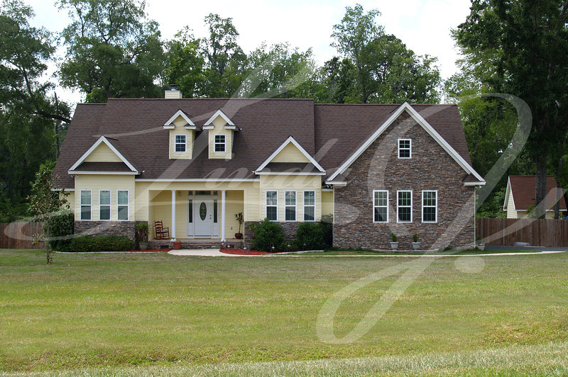 One story residential home with both brick and board siding on the facade.