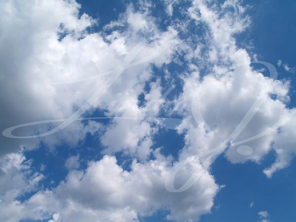 White puffy clouds in a blue sky.