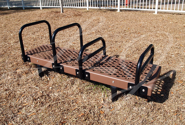 Brown and black bench dip exercise equipment in a park
