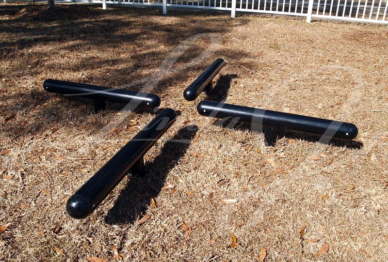 Black log hop exercise equipment in a park.