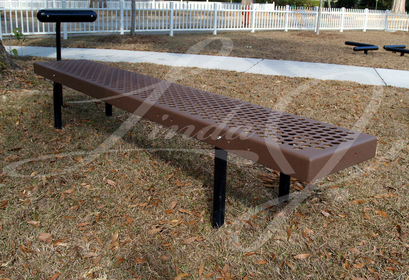 Brown and black curling bench exercise equipment in a park.
