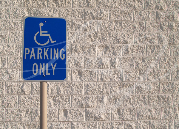 Blue handicap parking sign with a white textured concrete block background that can be used for copy space.