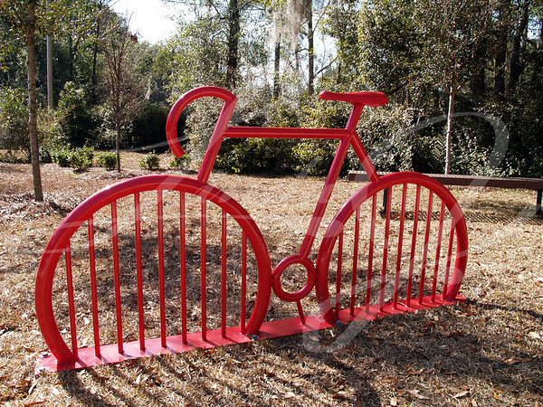 Red bike rack in a park shaped like a bike.