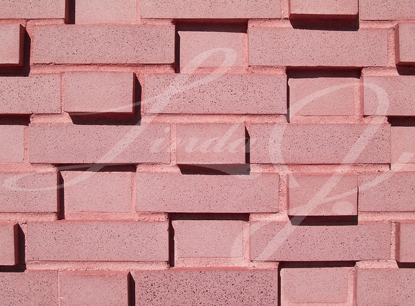 Pink  multi-layered and multi-sized painted brick wall.