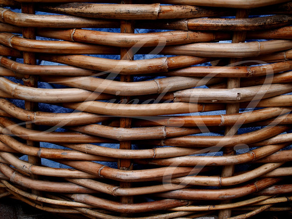 Weathered Wicker Basket---Weathered wicker basket  holding blue towels beside a hotel pool.