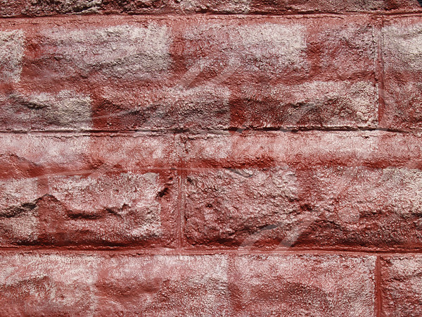 Textured concrete block wall painted to look like red bricks graffiti style.