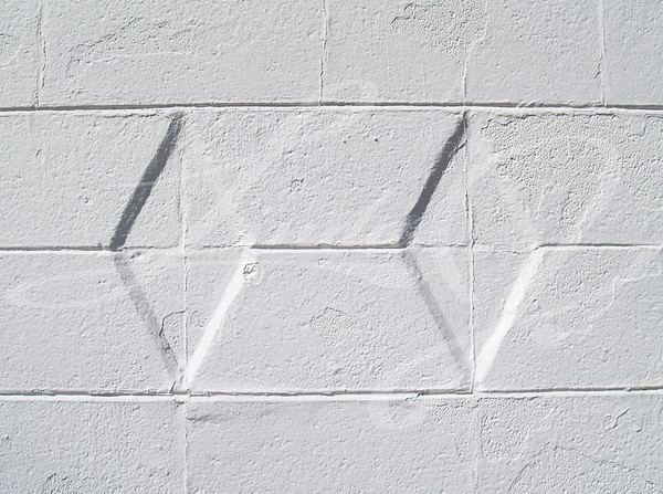 Close-up view of a white painted brick or block exterior wall with diamond texture.