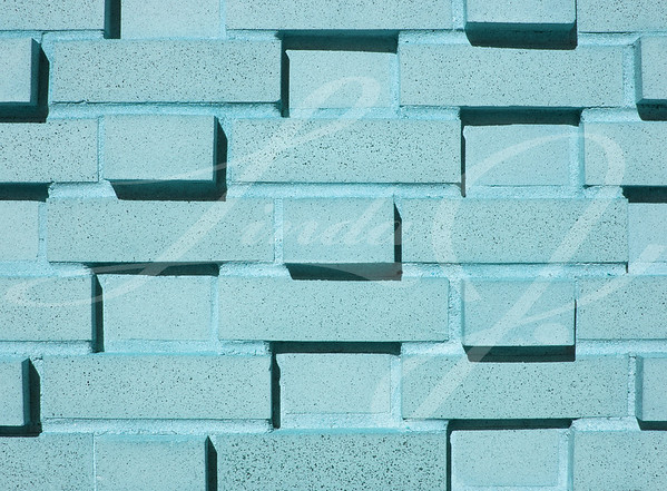 A pastel blue, teal or aqua multi-layered and multi-sized brick wall.