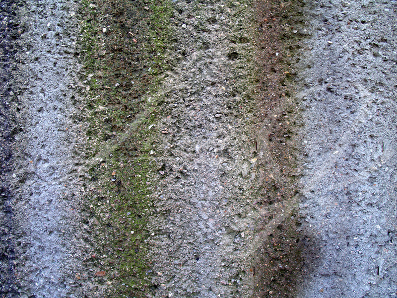 Weathered rough stucco or concrete retaining wall showing where rain has run down the side and discolored it.