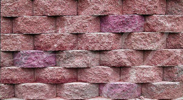 Blocks on a retaining wall in shades of red and pink.