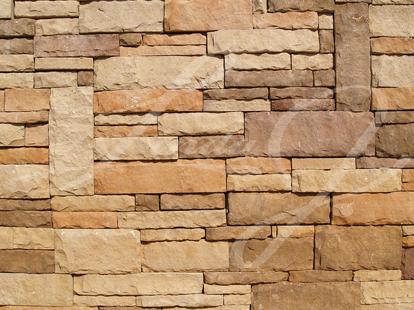 Multi-colored, sized and layered exterior stone wall.