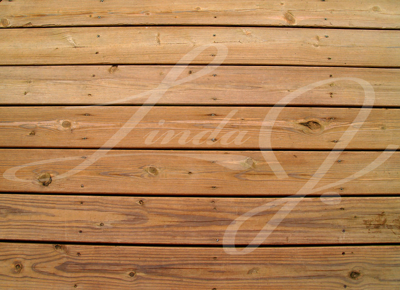 Wooden slats on a weathered wooden deck.