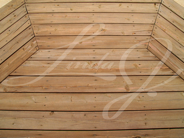 Wooden slats on a patterned weathered wooden deck.