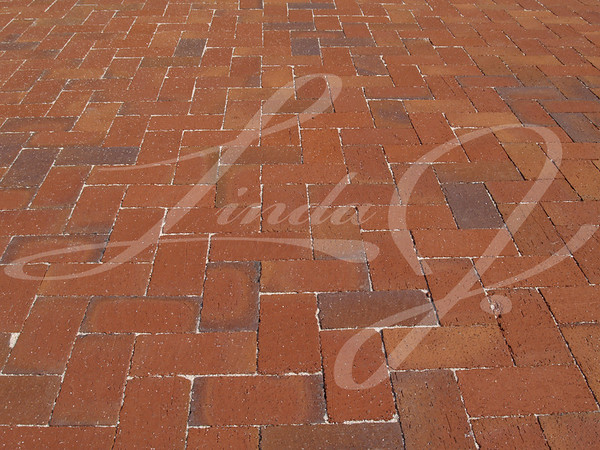 Multi-colored Red brick sidewalk laid in a herringbone pattern.