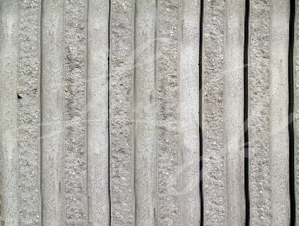 Rough textured concrete exterior striped wall with a vertical pattern.