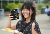 Kanako Hirano Psychology major from Tokyo Japan enjoys her food and makes pictures to send home, at the  WVU international student body picnic on the Lair green August 11, 2017. Photo Greg Ellis