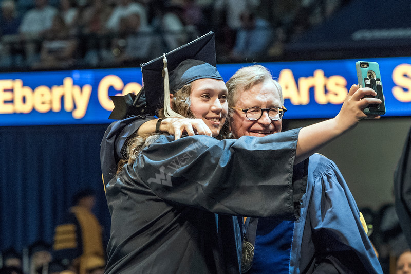 WVU Eberly College graduate Mikayla Johwson Biology major makes a selfie with WVU President E. Gordon Gee at the Eberly College Bachelor Commencement May 13, 2018. Photo Greg Ellis