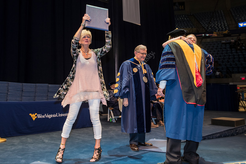 Carrie Dworshak holds up the posthumous degree belonging to her late son Calvin as her daughter Avery hugs Dean Dan Robison.  Calvin unexpectedly passed away last March and this would have been his commencement ceremony. He was recognized during the Davis College of Agriculture, Natural Resrouces and Design Commencement in the Coliseum May 11th, 2018.  Photo Brian Persinger