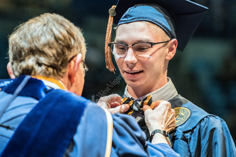 President Gordon Gee adjusts Jared Whiteds' bowtie upon crossing the platform to receive his degree at the Davis College of Agriculture, Natural Resrouces and Design Commencement in the Coliseum May 11th, 2018.  Photo Brian Persinger