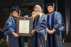 L to R WVU Provost Joyce E. McConnell presents an Honorary Doctorate of Letters to Ann Stuart Pancake with Mattew Valenti Chair, WVU Faculty Senate at the Eberly Graduate Commencement May 13, 2018. Photo Greg Ellis