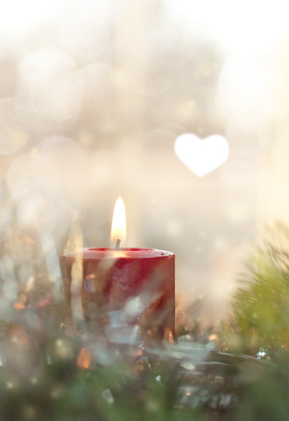 Dreamy image of a Red Christmas candle burning, surrounded by a wreath and decoration