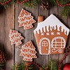 Christmas gingerbread house and fur tree cookies composition with xmas decorations on vintage wooden table background. Homemade traditional dessert food recipe.