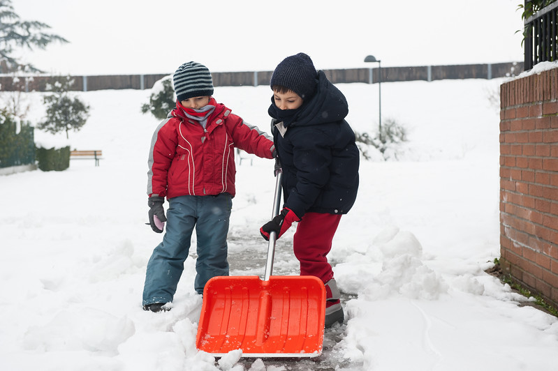 Young kids shoveling snow off sidewalk.