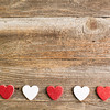 Four glitter hearts on reclaimed wood, valentines day background.