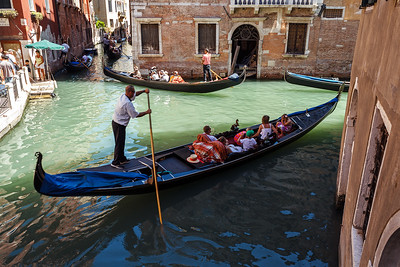 ITALY, VENICE - JULY 2012: Heavy traffic of gondolas with tourists cruising a small canal on July 16, 2012 in Venice. Gondola is a major mode of touristic transport in Venice, Italy.