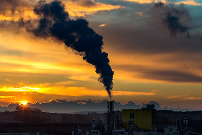 Sunrise silhouette of smoking factory