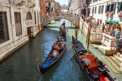 ITALY, VENICE - JULY 2012: Gondolas with tourists cruising a small Venetian canal on July 16, 2012 in Venice. Gondola is a major mode of touristic transport in Venice, Italy.