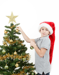 Boy with santa hat decorates the Christmas tree