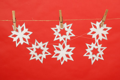 snowflakes produced by child hanging on red background