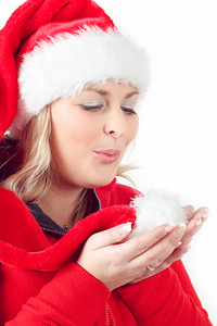 Portrait of joyful pretty woman blowing in red santa claus hat