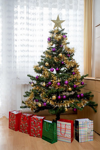 Decorated christmas tree with yellow and violet balls