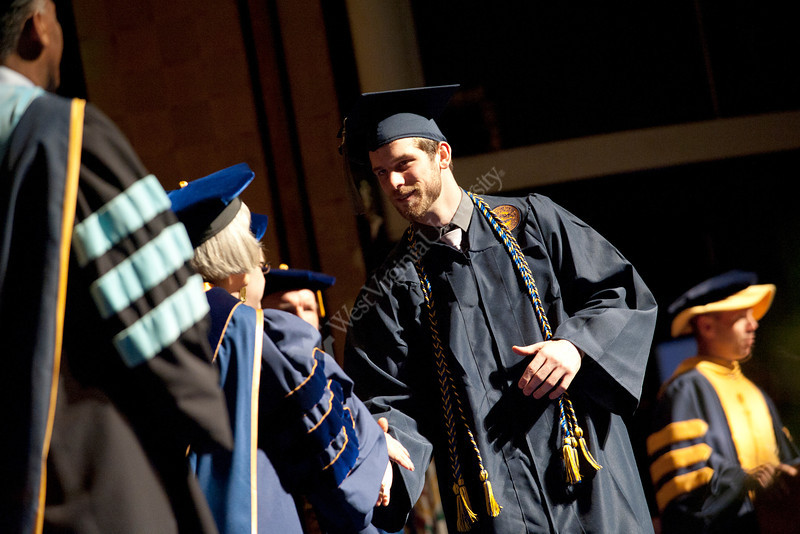 28346s038xx<br /> Kevin Dahl, a Sport and Exercise Psychology major, walks walks down the stage during the CPASS commencement ceremony.