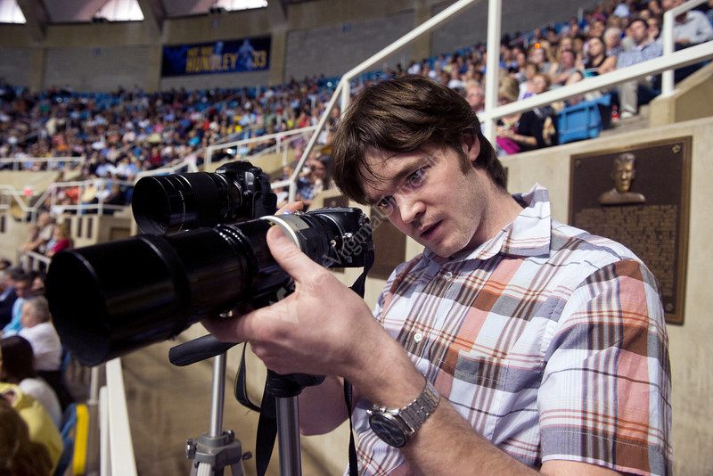 28343s0218xx John Donnelly of Ardmore, Pa checks focus on his Olympus camera waiting to photograph Brenden McCard an MDS major of Winwood, Pa in the Coliseum during the  Eberly Commencement Sunday May 13th, 2012. His second camera is a Nikon D50 with a 500mm f/8 Reflex-Nikkor C lens attached.