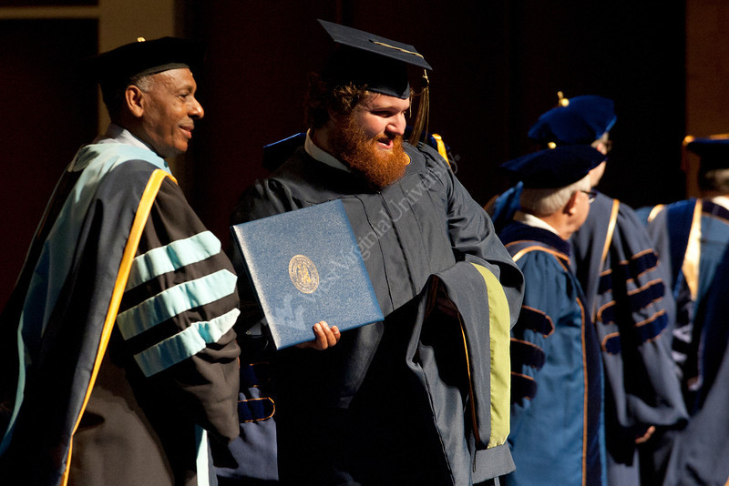 Former Mountaineer Brock Burwell receives his diploma for a masters in athletic coaching during the CPASS commencement ceremony.
