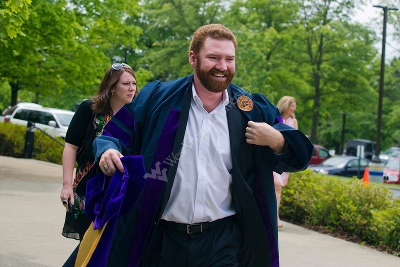 28331XX0006 Brady Cambell of Charleston, Wv puts on his robe and hat to take his place in the annual group shot preceding the College of Law Commencement at the Creative Arts Center Saturday May 12, 2012.