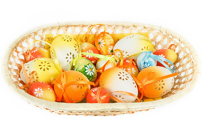 painted easter eggs with ribbon in basket on white