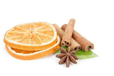 Star Anise, cinnamon and dried orange and green leave on white