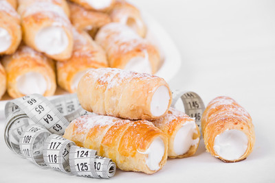 concept of slimming, cakes with measuring tape