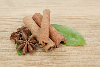 Star Anise, cinnamon and and green leave on wood