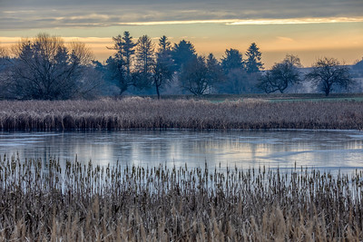 rural landscape with frozen small pond