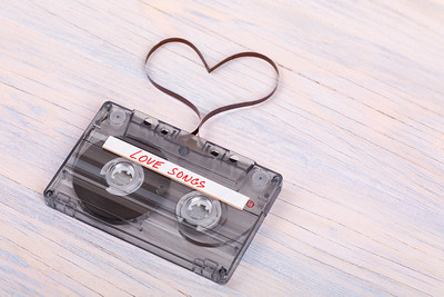 Audio cassette tape on wooden background. audio film shaping heart