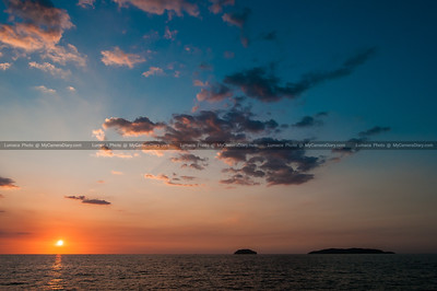 Sun Setting Below the Horizon By Two Island