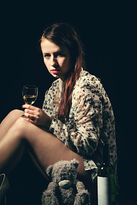 beautiful young brunette woman holding a bottle of white wine