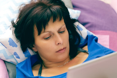 Middle age woman resting in bed with tablet